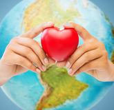 Woman hands holding red heart over earth globe