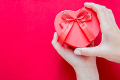 Woman hands holding red heart-shaped box Royalty Free Stock Images
