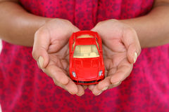 Woman hands holding red toy car Royalty Free Stock Image