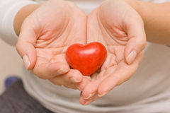 Woman hands holding a small red heart. Love. Happiness. Care. Healthcare. Valentine's day. Stock Image