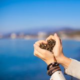 Woman hands holding small stones form heart shape Royalty Free Stock Photos