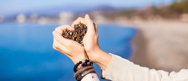 Woman hands holding small stones form heart shape royalty free stock image