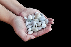 Woman hands holding small stones in hands isolated on black back Stock Photos