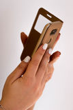 Woman hands holding smart phone. Woman hands with white nails holding a gold smart phone Royalty Free Stock Images