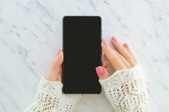 Woman hands holding smartphone on marble background with copy space. Flat lay. Top view. Woman using mock up mobile royalty free stock photography