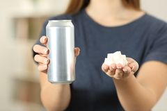 Woman hands holding a soda drink can and sugar cubes. Front view close up of a woman hands holding a soda drink can and sugar cubes at home Royalty Free Stock Photo