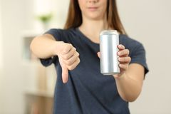 Woman hands holding a soda drink can with thumbs down. Front view close up of a woman hands holding a soda drink can with thumbs down at home Stock Photo