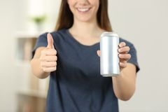 Woman hands holding a soda drink can with thumbs up. Front view close up of a woman hands holding a soda drink can with thumbs up at home Stock Photos