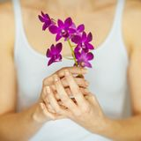 Woman hands holding some violet orchid flowers, sensual studio shot Stock Image