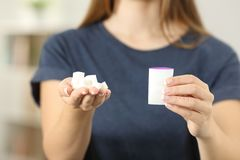 Woman hands holding sugar cubes and saccharin Royalty Free Stock Photos