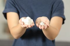 Woman hands holding sugar cubes and saccharin pills stock photo