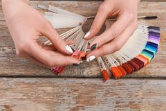 Woman hands holding summer nail samples. Young woman hands holding nails colors samples on vintage wooden background. Nail beauty salon Stock Photography