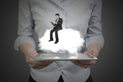 Woman hands holding tablet with businessman sitting on cloud Stock Image
