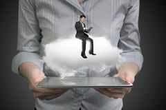 Woman hands holding tablet with businessman sitting on cloud Stock Photos