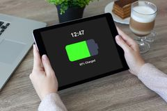Woman hands holding tablet with charged battery screen in cafe Royalty Free Stock Images