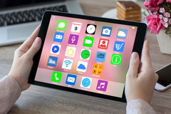 Woman hands holding tablet computer with home screen icons apps. And notebook Royalty Free Stock Image