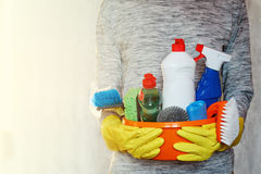 Woman hands holding tub with cleaning supplies. Royalty Free Stock Photography