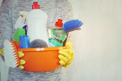 Woman hands holding tub with cleaning supplies. Stock Photography