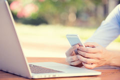 Woman hands holding, using smart, mobile phone and computer. Closeup image woman hands holding, using smart, mobile phone and computer isolated outside city royalty free stock photo