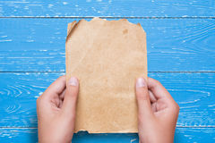 Woman hands holding vintage paper sheet over aged blue wooden ta. Ble. Vertical Stock Photography