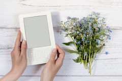 Woman hands holding white ebook with flowers in background Royalty Free Stock Photo