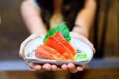 Woman hands holding white plate with Salmon sashimi Stock Image