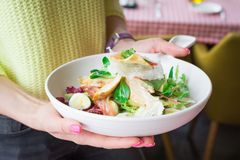 Woman hands holds big white plate with italian salad. In a restaurant royalty free stock photo