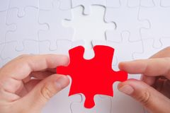 Woman hands holds the last puzzle piece of a Jigsaw puzzle Stock Image