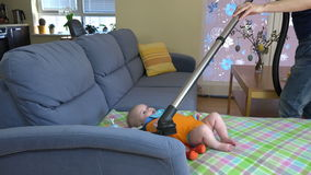 Woman hands hoover dust from sofa around baby daughter. 4K stock footage