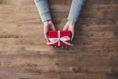 Free Woman Hands In Gray Sweater On Wood Table Giving Red Christmas Gift Box Wrapped With White Ribbon Stock Image - 104108761