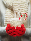 Woman Hands In Woolen Red Gloves Holding Cozy Mug With Hot Cocoa, Tea Or Coffee And Candy Cane. Winter And Christmas Time Concept.