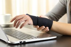 Woman hands with injured wrist complaining. Close up of a woman hands with injured wrist complaining using a laptop at home royalty free stock photos