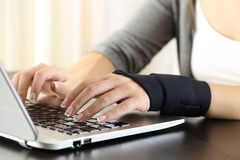 Woman hands with injured wrist working on line. Close up of a woman hands with injured wrist working on line with a laptop on a desk in a house interior royalty free stock photography