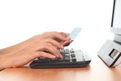 Woman hands in a keyboard with a credit card. On a white  background Royalty Free Stock Image