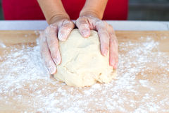 Woman hands kneading dough. On a dusted cutting board Stock Photos