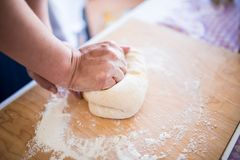 Woman hands kneading pasta dough bread. On a wooden table Stock Photo