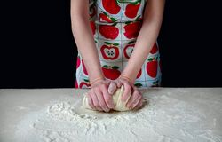 Woman Hands Kneads the Dough with White Flour on the Kitchen Table on a Dark Background Royalty Free Stock Photography