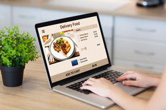 Woman hands laptop with delivery food on screen in room Royalty Free Stock Photo