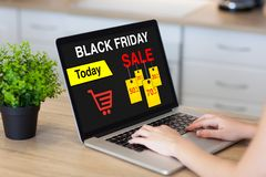 Woman hands in laptop with sale black friday on screen Royalty Free Stock Photo