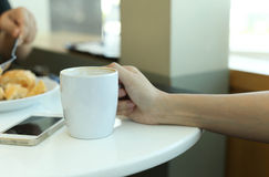 Woman hands with latte coffee and cellphone Royalty Free Stock Photos