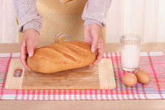 Woman hands laying the bread, table, milk and eggs Royalty Free Stock Photo