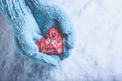 Woman hands in light teal knitted mittens are holding beautiful entwined vintage red heart on snow. Love, St. Valentine concept. Stock Photos