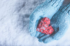 Woman hands in light teal knitted mittens are holding beautiful a entwined vintage red heart on snow. Love, St. Valentine concept Royalty Free Stock Photos