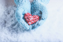 Woman hands in light teal knitted mittens are holding beautiful entwined vintage red heart on snow. Love, St. Valentine concept. Royalty Free Stock Photos