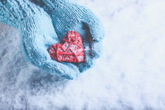 Woman hands in light teal knitted mittens are holding beautiful entwined vintage red heart on snow. Love, St. Valentine concept. Stock Images