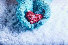 Woman hands in light teal knitted mittens are holding beautiful entwined vintage red heart in a snow. St. Valentine concept. Royalty Free Stock Photography
