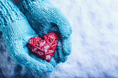 Woman hands in light teal knitted mittens are holding beautiful entwined vintage red heart in a snow. St. Valentine concept. Stock Photo