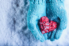 Woman hands in light teal knitted mittens are holding beautiful entwined vintage red heart in a snow. St. Valentine concept. Stock Image