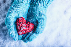 Woman hands in light teal knitted mittens are holding beautiful entwined vintage red heart in a snow. St. Valentine concept. Royalty Free Stock Photos