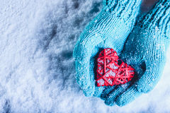 Woman hands in light teal knitted mittens are holding beautiful entwined vintage red heart in a snow. St. Valentine concept. Stock Images